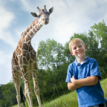 Boy standing in front of giraffe