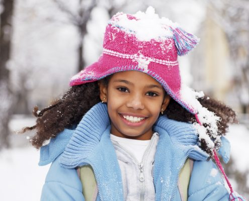 Happy girl surrounded by snow with snow covering her hat.   [url=http://www.istockphoto.com/search/lightbox/9786682][img]http://dl.dropbox.com/u/40117171/children5.jpg[/img][/url]